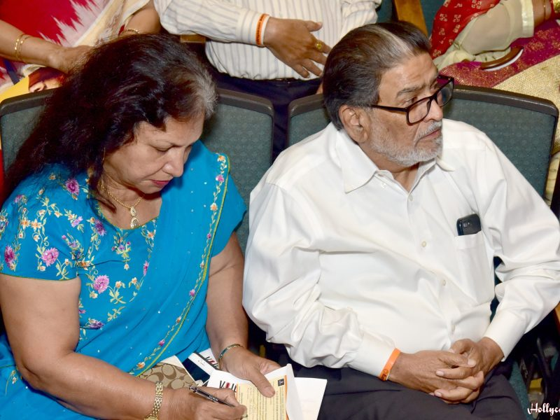 Late Shri Ukabhai and Nalini ji writing their pledge of $10,000